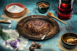 Food photography of chocolate brownie on brown plate and blue board